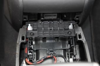 Pohled na diagnostický konektor po vyjmutí plastu pod ruční brzdou.