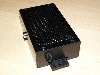 Mikropočítač Raspberry Pi v krabičce EM-RASPBERRY B+(Black) společnosti EMKO.cz s doplněným DC/DC zdrojem RASP-PSM. Vedle slotu paměťové SD karty přibyl napájecí konektor zdroje RASP-PSM