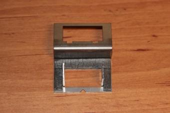 Nalepená tlumící páska na držáku.